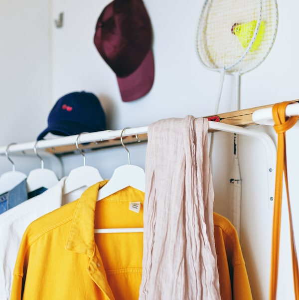 A hallway wall with clothes on white hangers, scarves, hats and accessories, all on and around a white MULIG clothes bar.