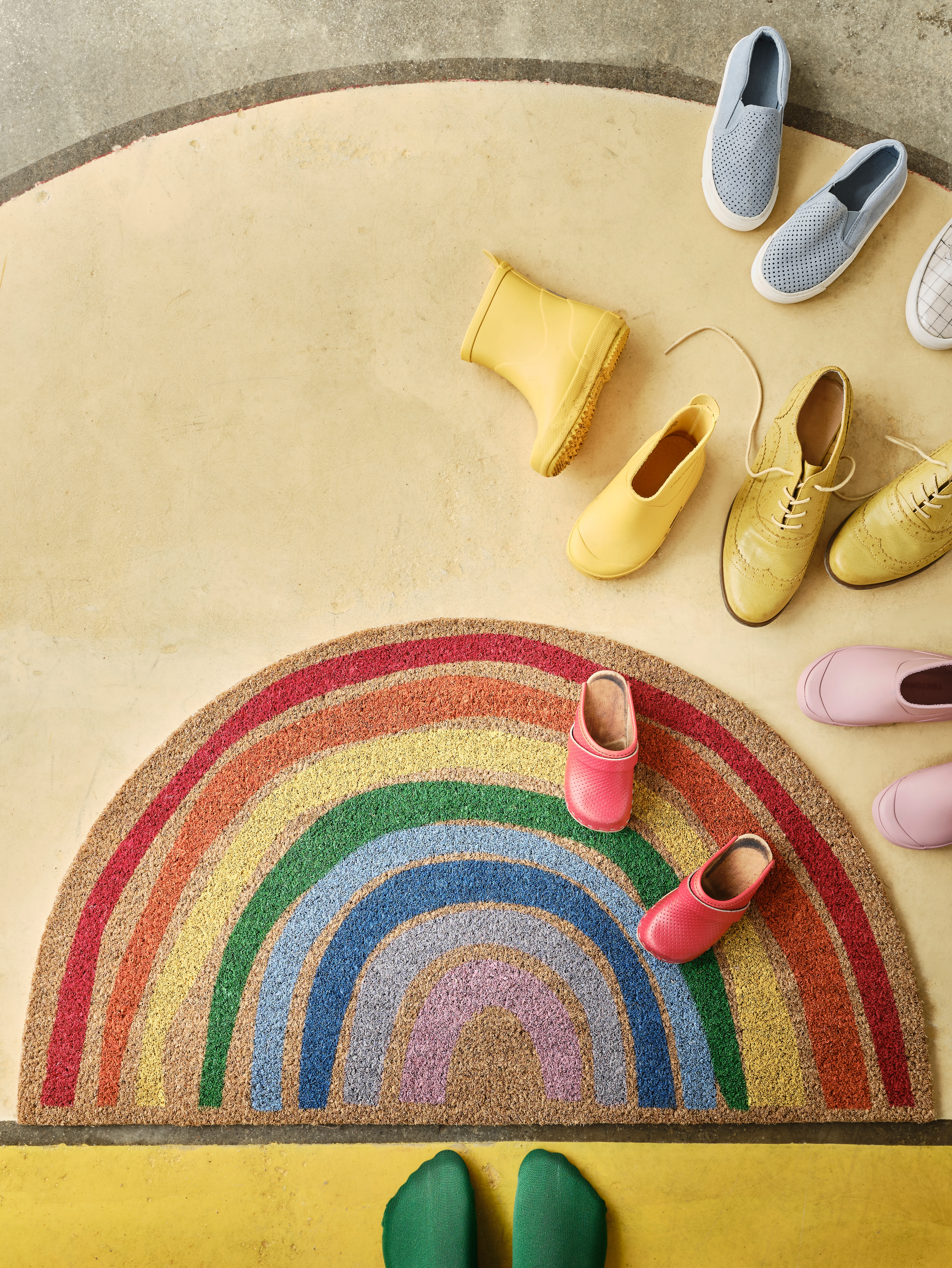 PILLEMARK door mat with a rainbow pattern lying on a yellow floor with colourful shoes and a pair of feet with green socks.