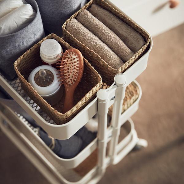 Une desserte RÅSKOG blanche contenant des boîtes LURPASSA en jonc de mer, remplies de textiles et d'accessoires.