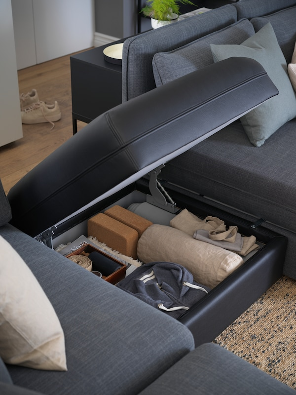 A VALLENTUNA seat module with storage, in Gunnared medium grey, the top open with various yoga accessories inside.