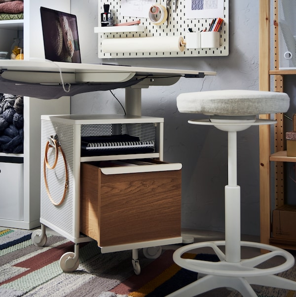 A white BEKANT desk and drawer unit, a beige LIDKULLEN sit/stand support, a white SKÅDIS pegboard and two shelving units.