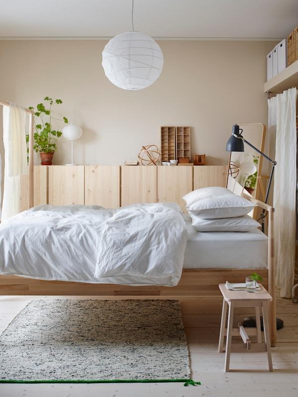 Une chambre lumineuse avec un lit double et une armoire en bois massif tapissant un mur
