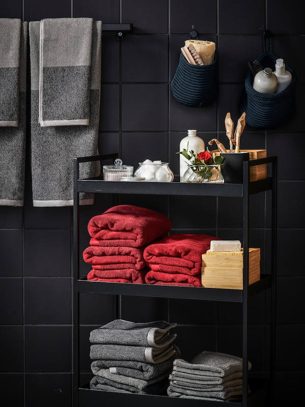 A bathroom cart stocked with red and grey towels, in a bathroom space with black tiles on the wall.