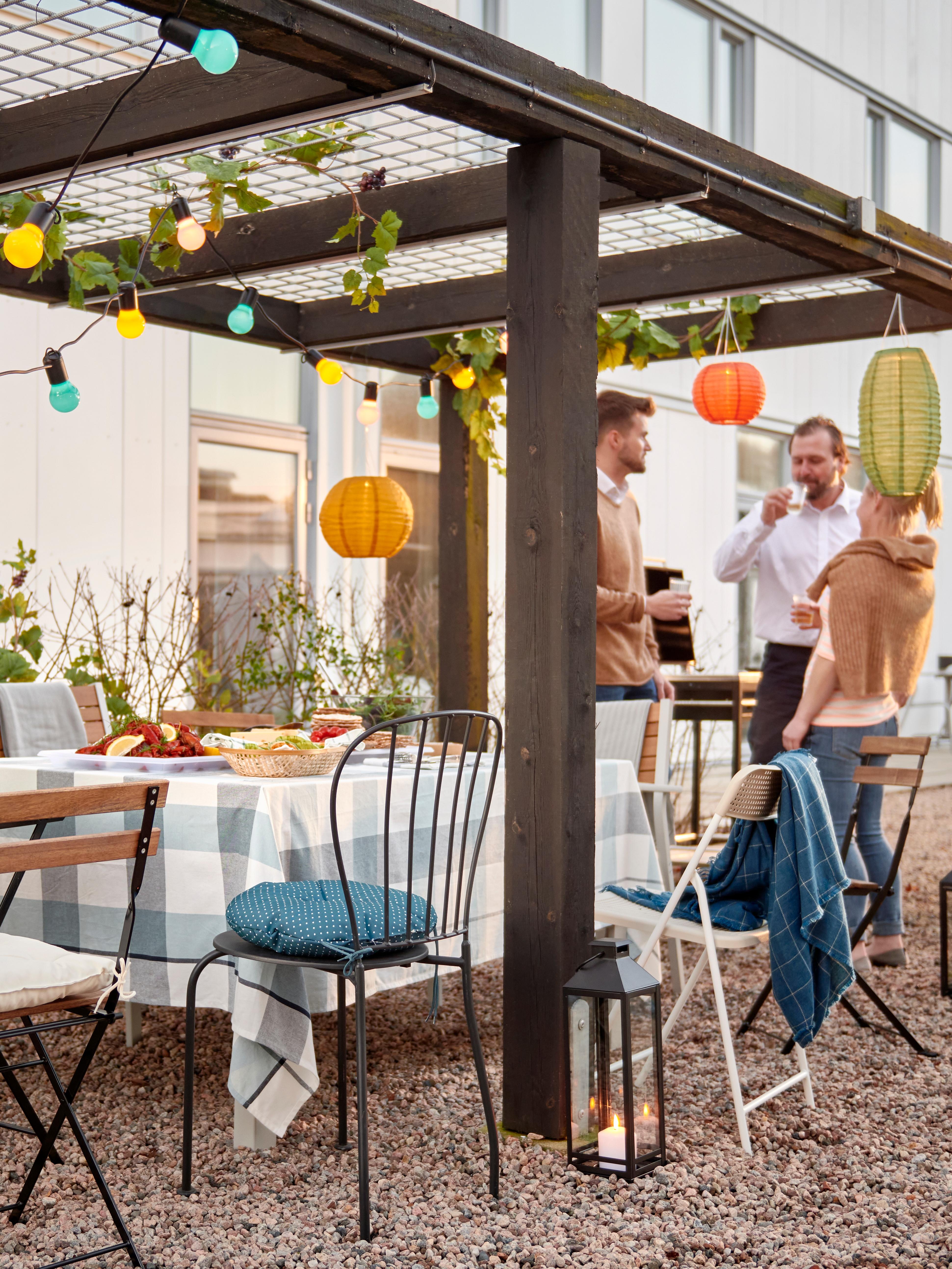 Uno spazio all'aperto con un gruppo di persone che socializzano insieme, un tavolo apparecchiato per una festa, sedie e illuminazione sospesa.