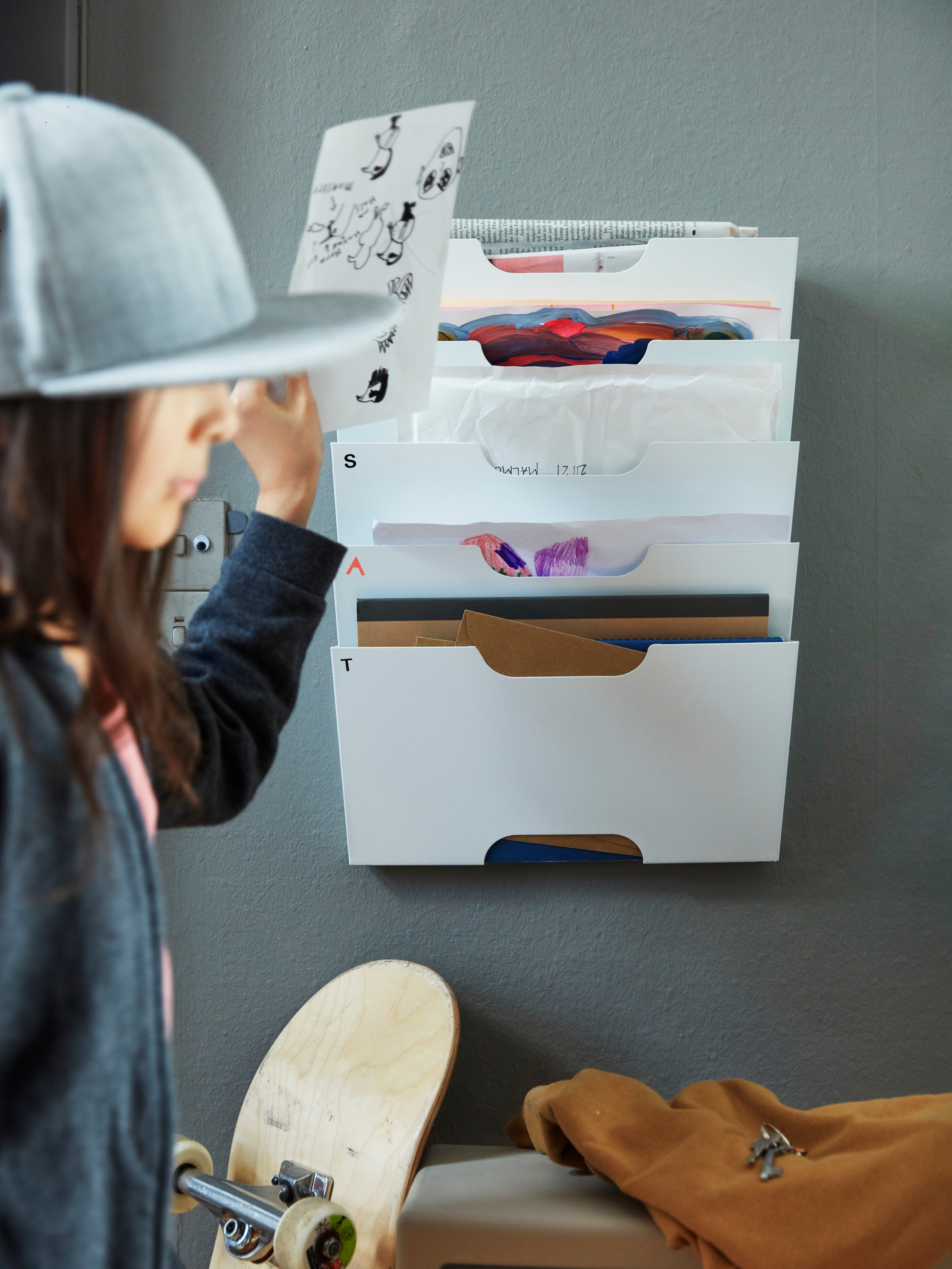 A person wearing a cap and carrying a skateboard puts a card into a white KVISSLE wall newspaper rack on the wall.