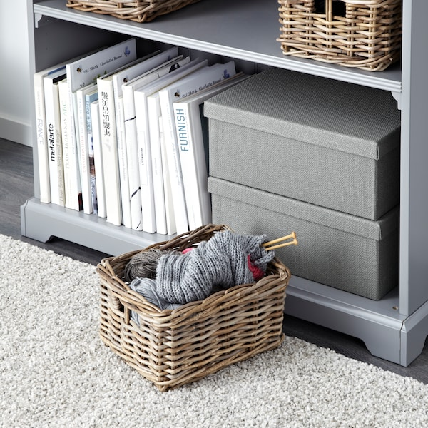 A close up of a grey bookshelf with a brown basket with knitting materials.