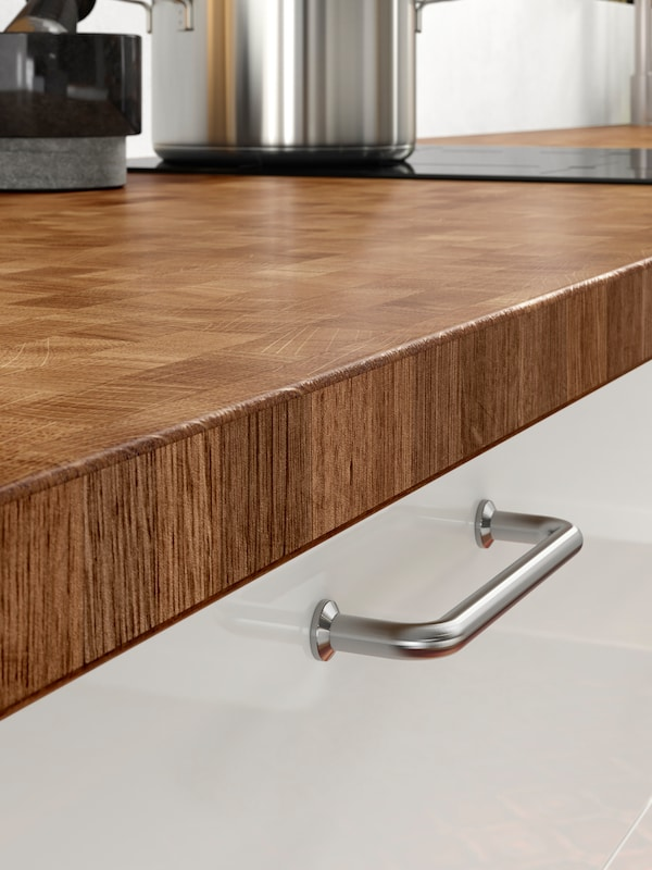 A close-up of the durable SKOGSÅ worktop in oak in a kitchen setting.