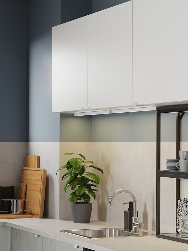 Kitchen with white cabinets, black open shelves, concrete-effect fronts, a mixer tap in zinc and LED lighting strips.