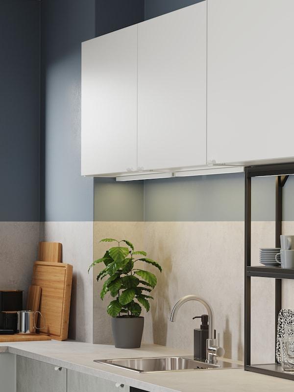 Kuchyně s bílými skříňkami, černé otevřené police, čela skříněk v imitaci betonu, zinková mísicí baterie a osvětlovací proužky LED.