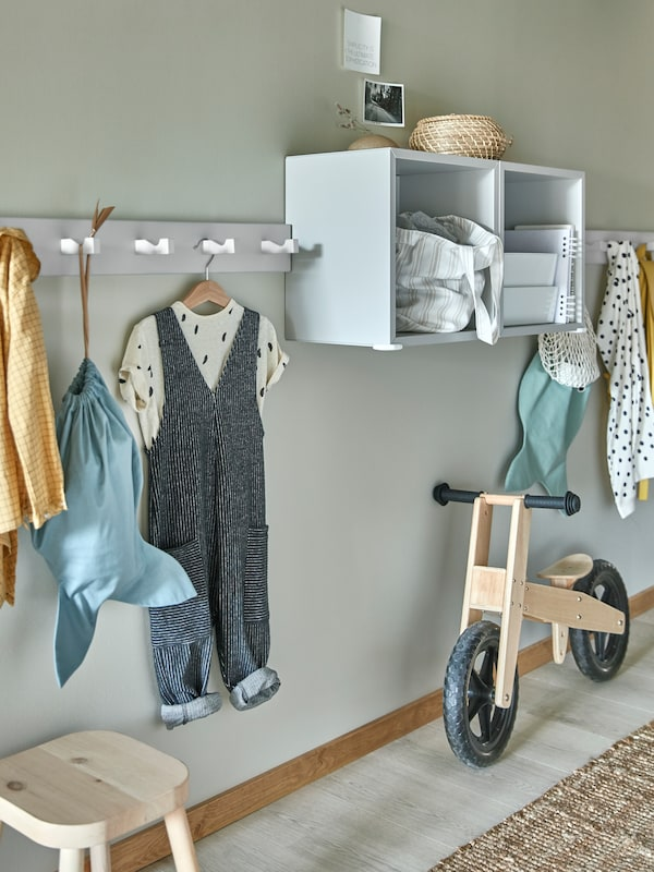 A hallway with a KUBBIS hook rack holding children's clothing and a bag beside two EKET cabinets on the wall.