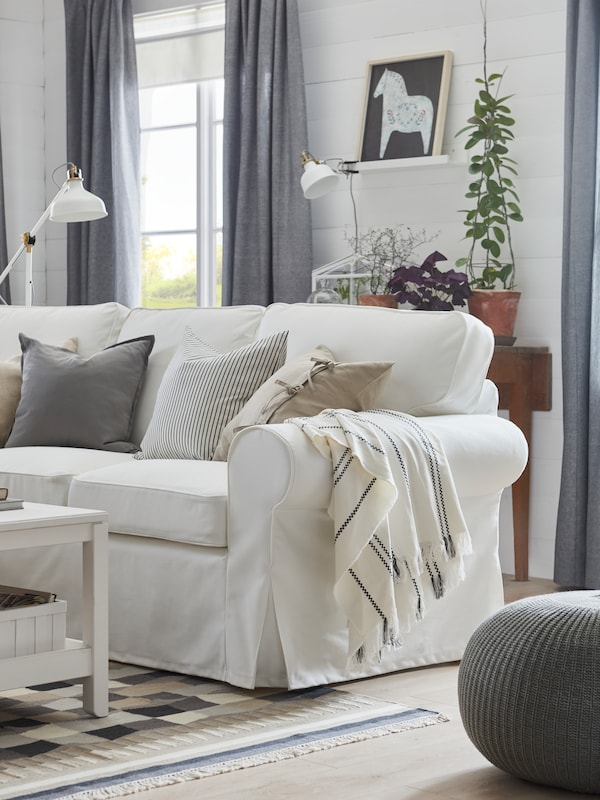 Cotton STINAMAJ throw, in white and dark grey, draped over the arm of a white EKTORP sofa in a living room.