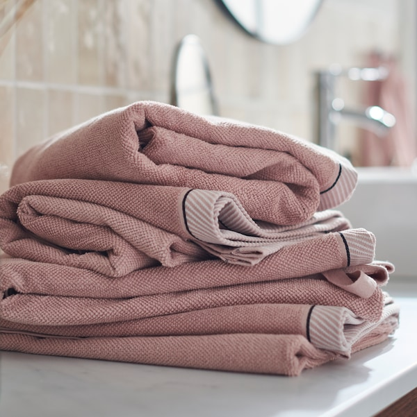 Stack of folded light pink VIKFJÄRD in a bathroom.