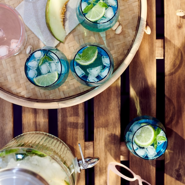 Puinen pöytä, jolle on katettuna hanallinen VARDAGEN-purkki sekä SOMMARDRÖM-tarjotin, jolla on IVRIG-laseja. Laseissa on jäitä, sitruunaa ja limonadia.