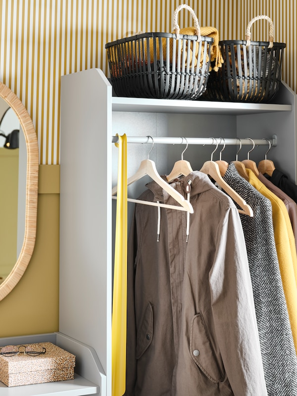Part of a grey HAUGA open wardrobe, shirts on hangers in a row, a single hanger with a dress hanging from the top edge.