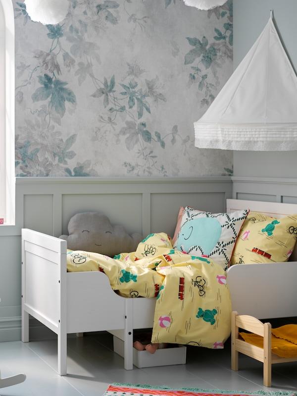 Cadru de pat extensibil SUNDVIK, alb cu lenjerie de pat galbenă.   Deasupra, un baldachin montat de perete, pentru o atmosferă de confort.