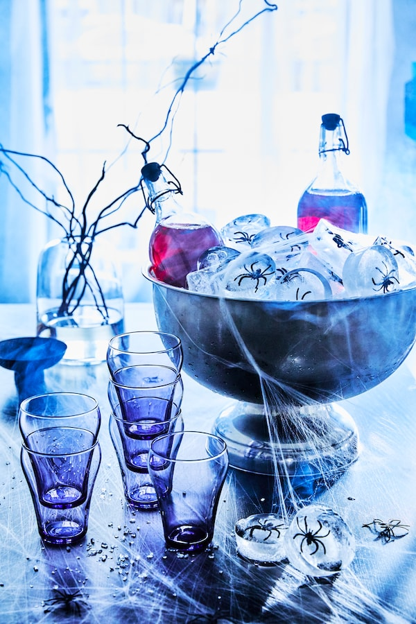 A Halloween-inspired table, with Lingonberry drink in KORKEN bottles with stoppers in a large bowl with ice cubes with plastic spiders in them sit on a table with cups and spider webs.