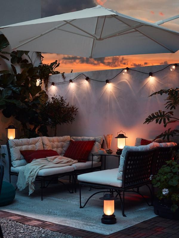 Une terrasse confortable dans une ambiance de coucher de soleil, avec des meubles de jardin entourés de lampes solaires.