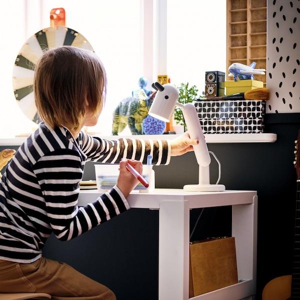 Cozinha de brincar NYBAKAD com porta deslizante por baixo de uma calha na parede com utensílios de cozinha de brincar DUKTIG.