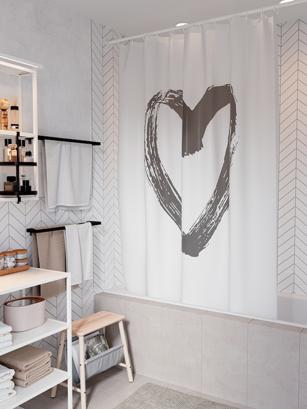 A white shower curtain with a large grey heart.