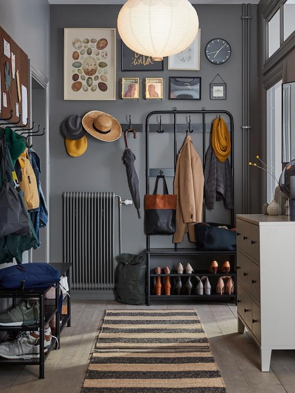 Szürkére festett előszoba PINNIG kabátakasztóval, paddal és egy sor horoggak, amiken ruhák lógnak, alul a cipőtartón cipők, a földön egy szőnyeg.