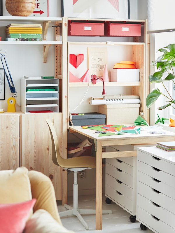 A corner of a room with solid pine IVAR shelves and a desk with coloured paper on it, and two white ALEX drawer units.