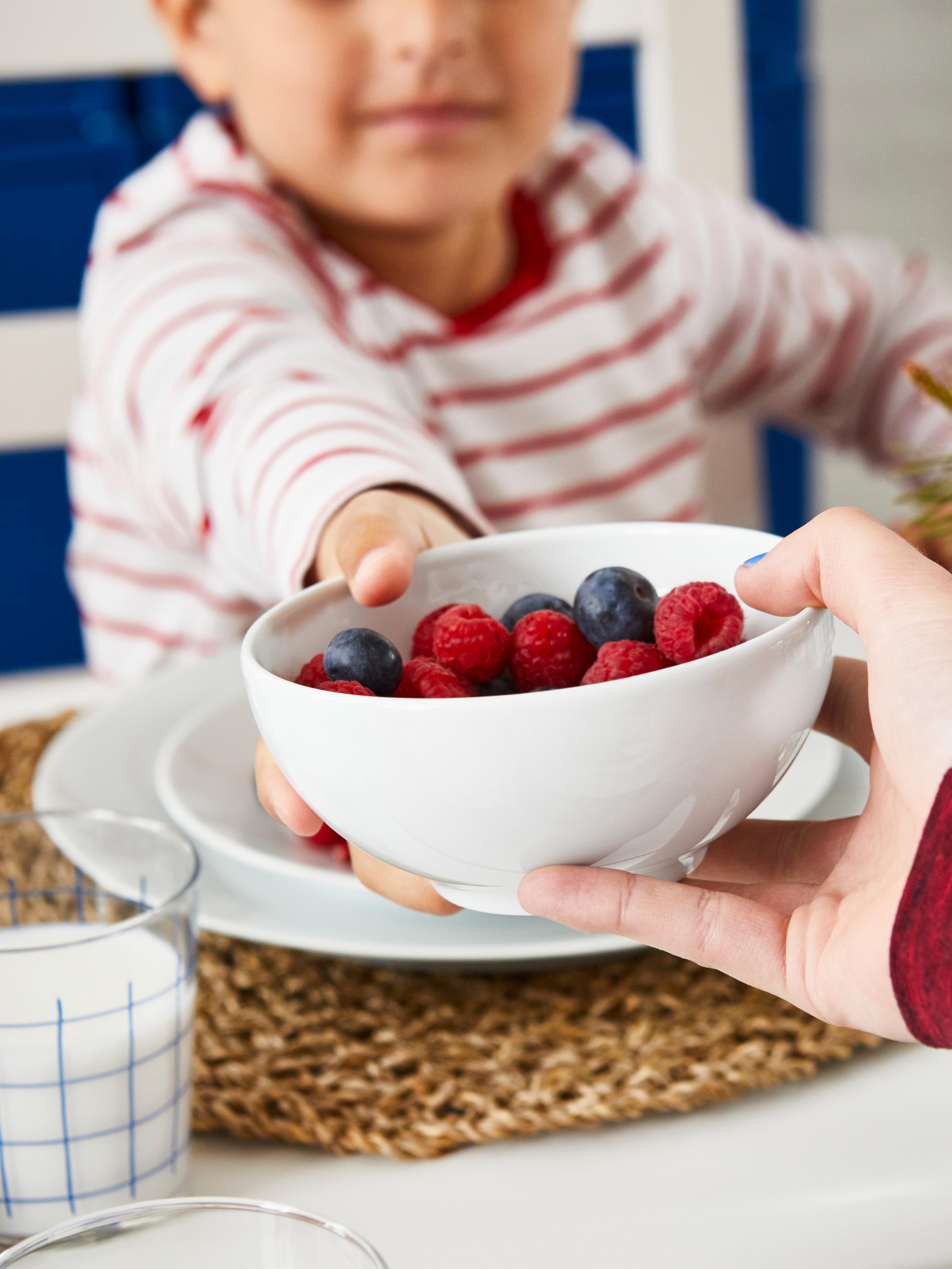 Malom djetetu u majici s bijelim i crvenim prugama dodaje se IKEA 365+ zdjela puna bobičastog voća.