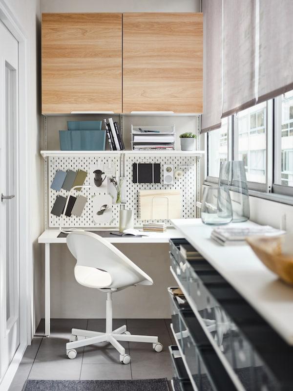كرسي دوار بيج/أبيض، مكتب أبيض، ألواح تعليقبيضاء، نظام تخزين ورفوف BOAXEL، بالإضافة إلى خزائنENHET باللون الأبيض/بلوط.