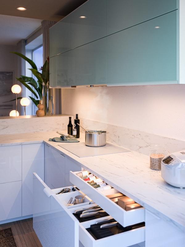 Hämärä keittiö jossa on yläkaapeissa vaaleansiniset JÄRSTA- kaapin ovet ja alakaapeissa valkoiset RINGHULT- laatikon etusarja. Työtasona keittiössä on valkoinen marmorikuvioinen EKBACKEN-työtaso.