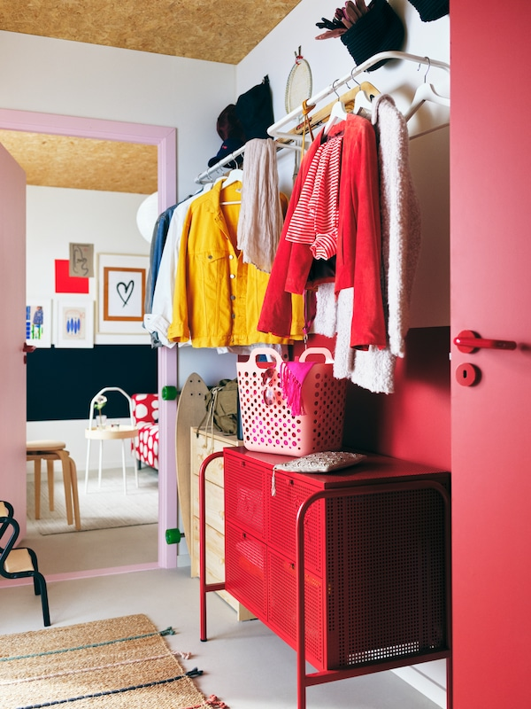 A colourful hallway arrangement with garments on white MULIG clothes bars on the wall above a red NIKKEBY chest of drawers.