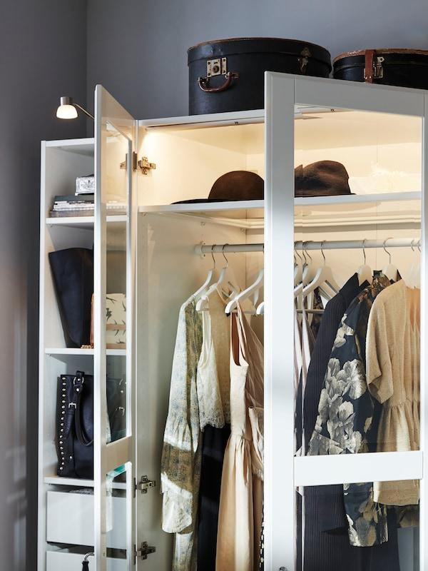 Parte de uma estante aberta PLATSA em branco, com caixas e roupas nas prateleiras e outras roupas penduradas num varão.