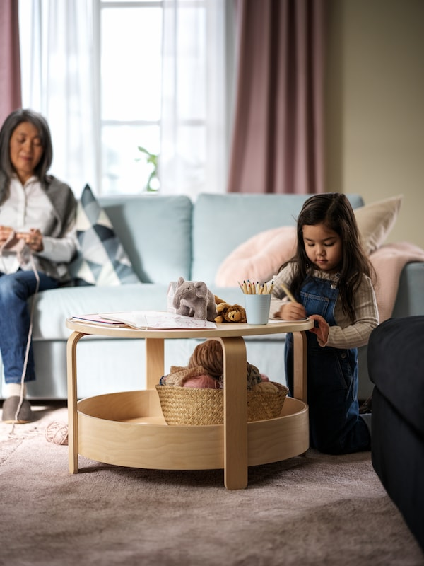 A living room where a girl plays at a BORGEBY birch-veneer coffee table, and a woman crochets in a light-blue VIMLE sofa.
