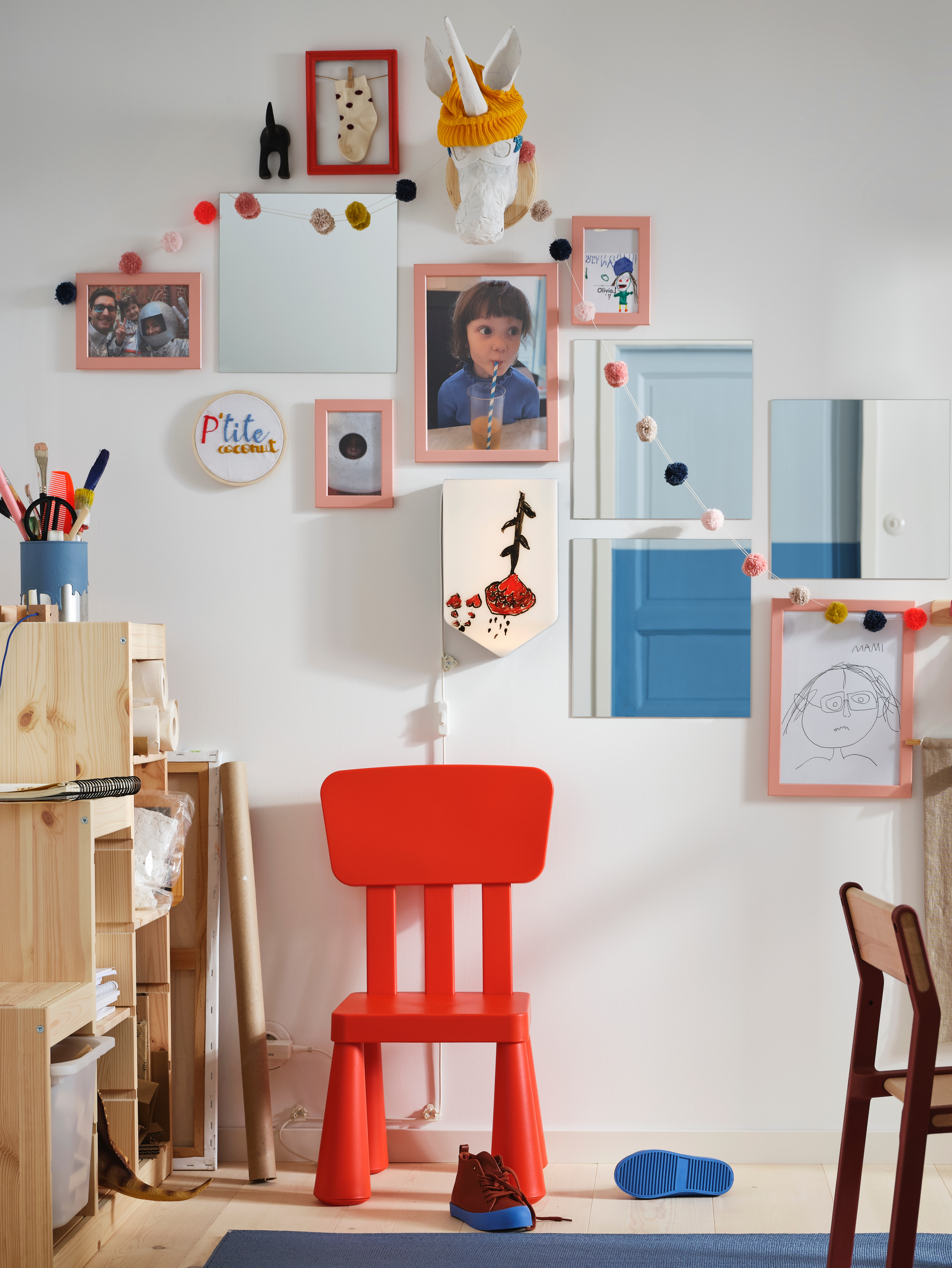A red MAMMUT chair by a TROFAST storage unit against a white wall covered with FISKBO frames holding children's pictures.