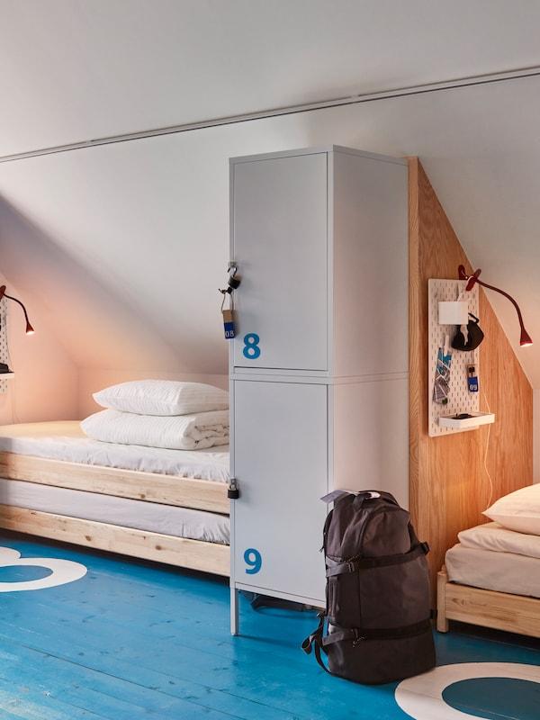 Camera da letto con soffitto spiovente e pavimento blu con due zone notte arredate con letti UTÅKER e mobili con lucchetto.