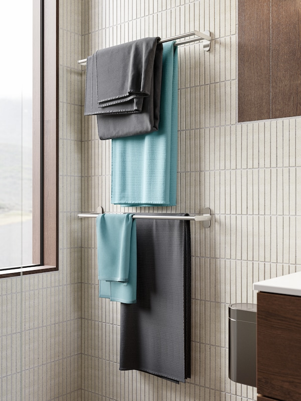 Cream narrow bathroom tiles, two rails beside a window with grey and blue-green towels hanging on them.