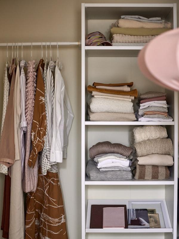 Un lit matelassé gris et une armoire-penderie blanche sont placés contre un mur blanc.