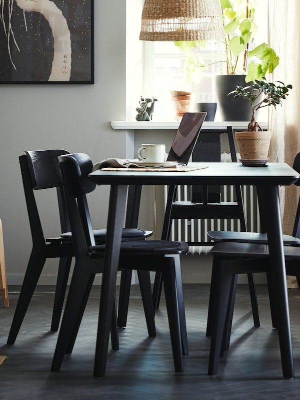 A black LISABO table with 4 chairs by a window, with an open laptop, a cup of coffee and a plant on it.
