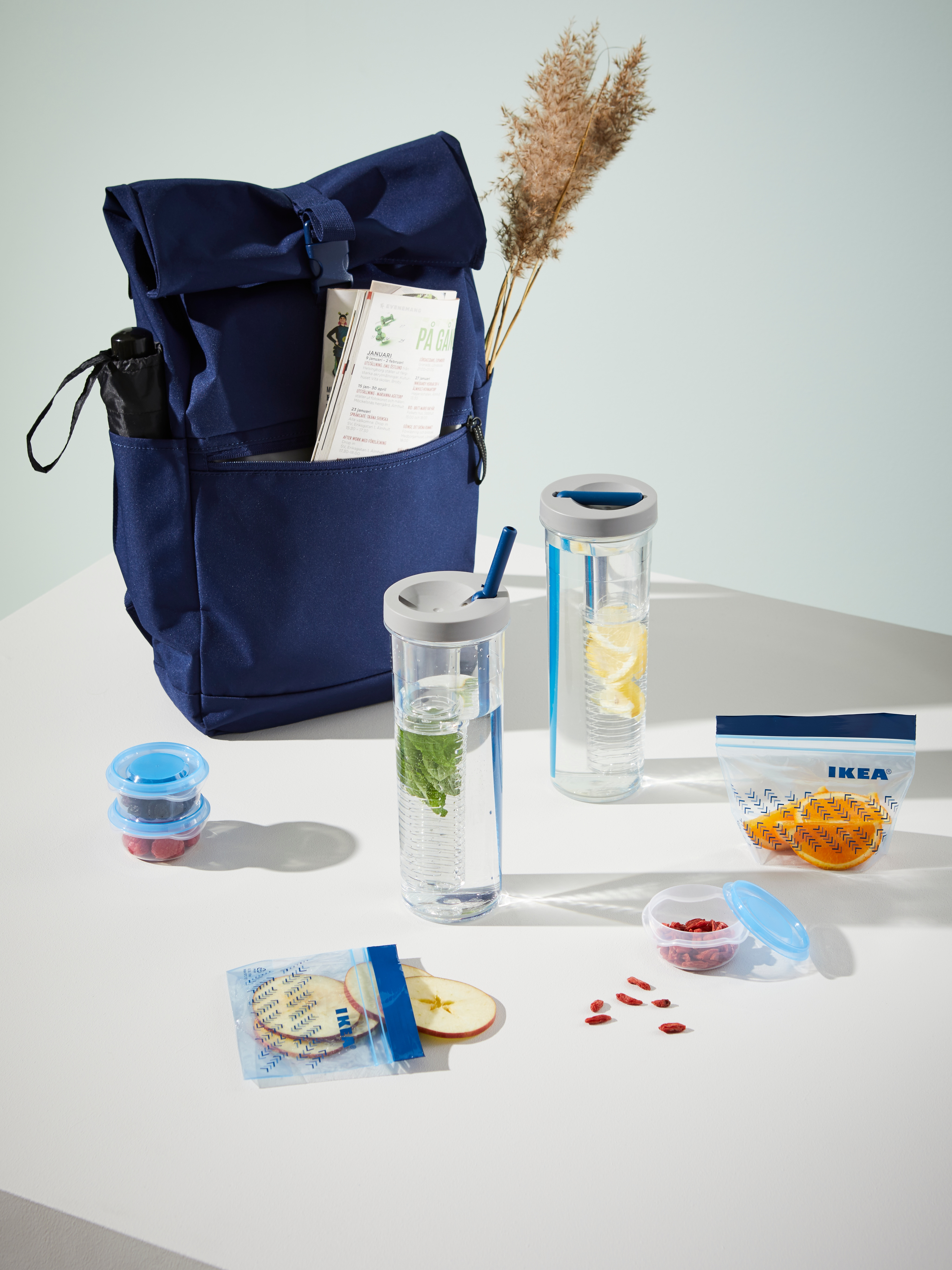UPPLADDA infusion bottles with straws, water and cut fruit on a table with a STARTTID backpack and food bags and containers.