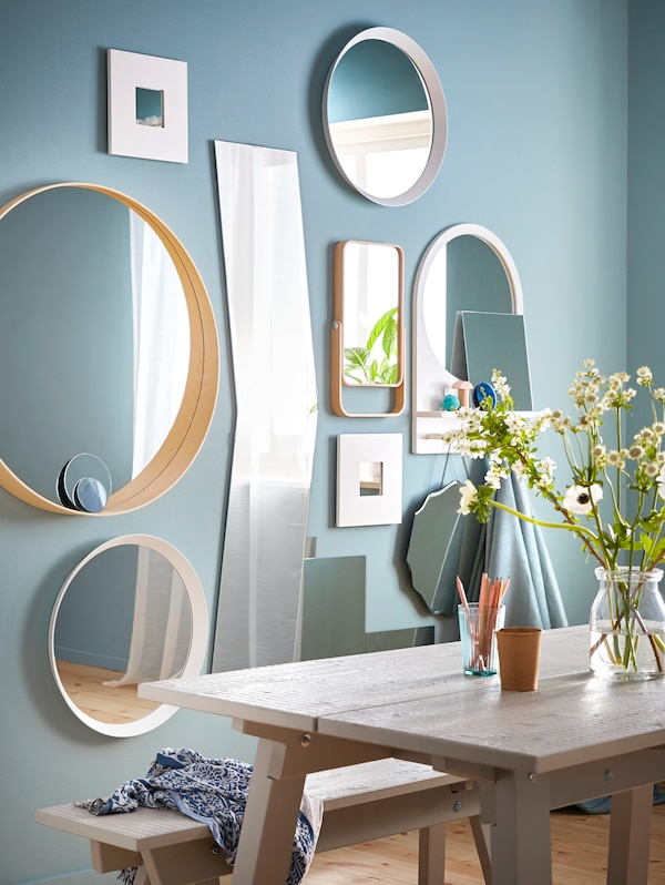 A green wall with a gallery of mirrors in different shapes and sizes.
