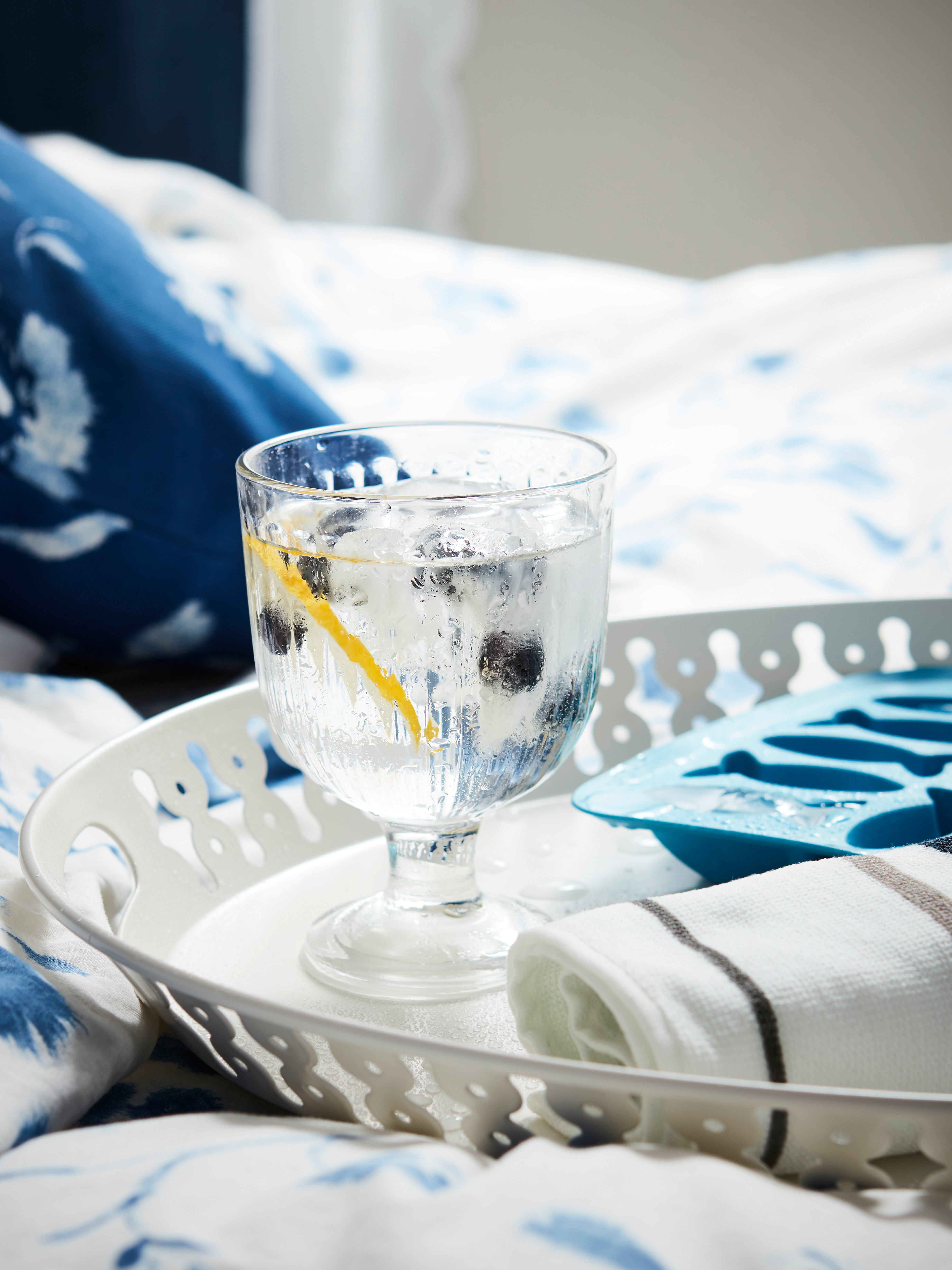 A white ROMANTISK tray with glass goblet and an ice cube tray on a bed with blue and white quilt cover and pillowcase.