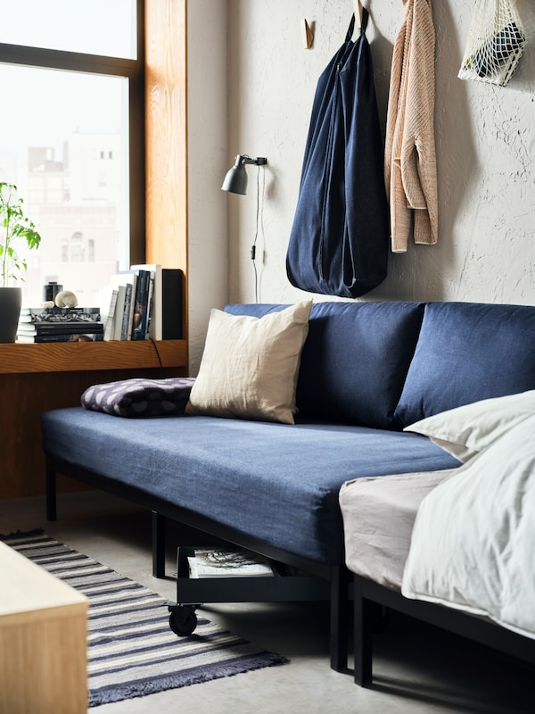 A dark blue RÅVAROR daybed is set against a concrete-style wall. A RÅVAROR storage bag has been hung above it.