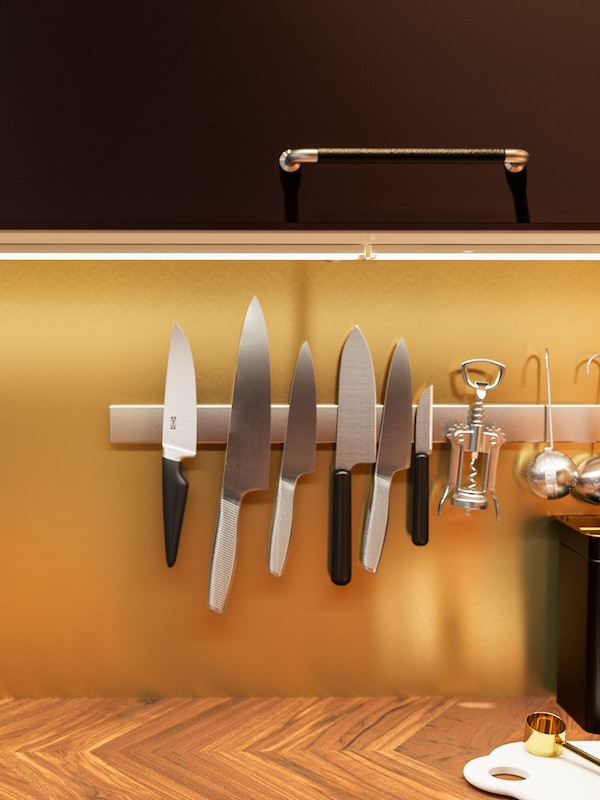 A magnetic knife rack with knives on a brass-colored wall panel above a worktop in walnut with worktop lighting.