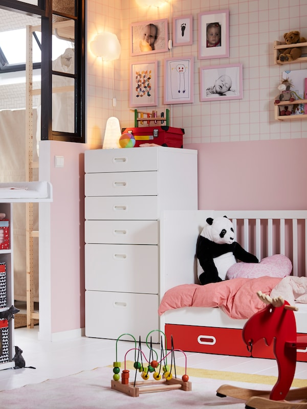 A STUVA/FRITIDS crib with drawers with a panda toy on it, next to a STUVA/FRITIDS chest of 6 drawers in a pink bedroom.