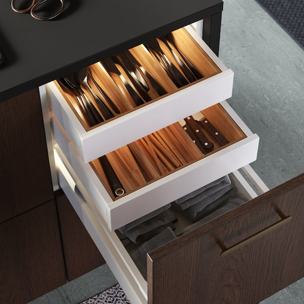 A SINARP drawer with kitchen towels is pulled out revealing two more white drawers with VARIERA cutlery trays in bamboo.
