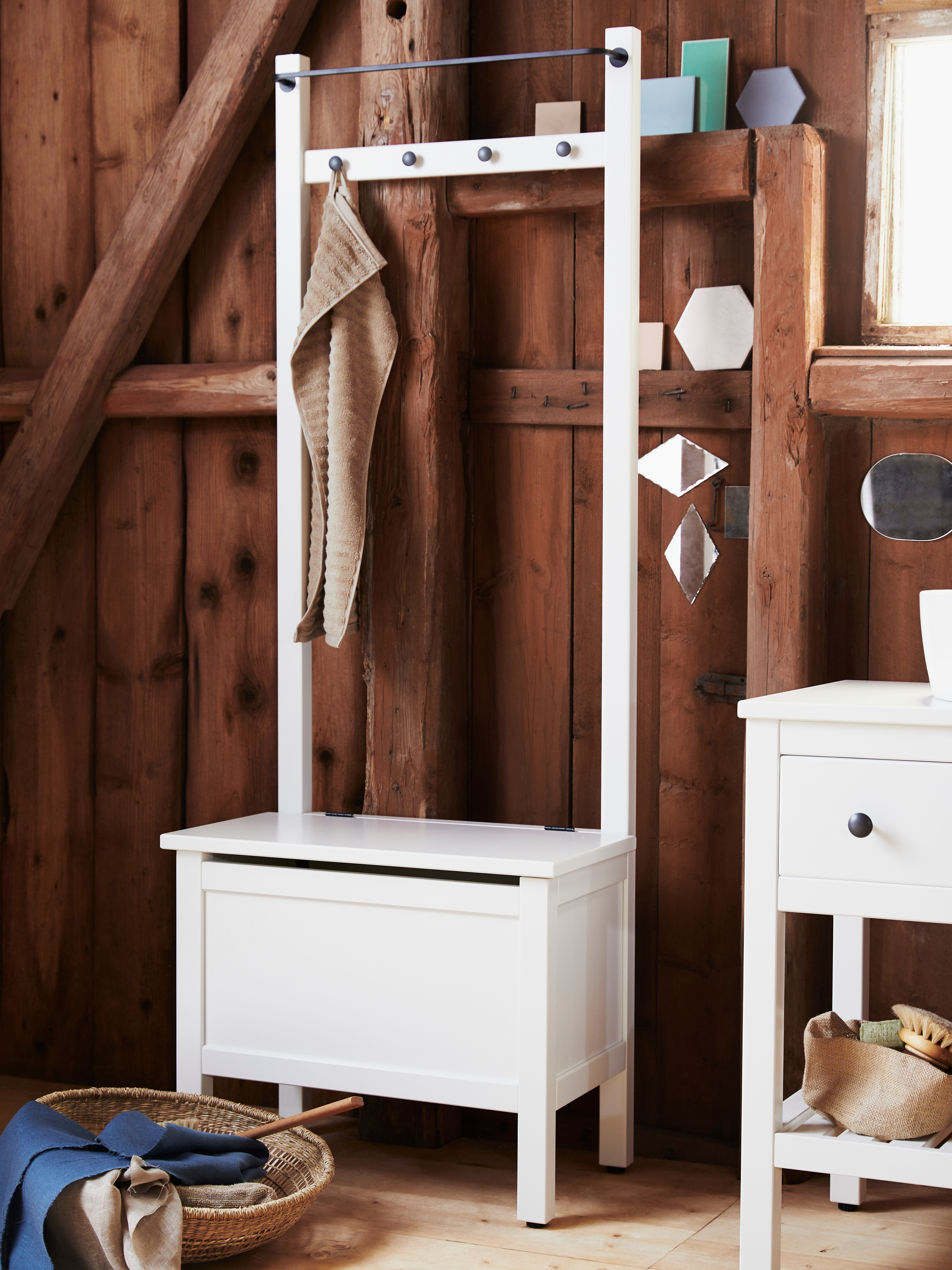 A wood-panelled bathroom wall that has a white HEMNES storage bench, with towel rail and four hooks, and a towel on one hook.