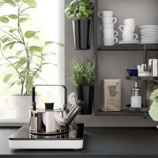Un bollitore su un piano cottura a induzione portatile accanto al quale c'è uno scaffale a giorno ENHET nero dove sono riposti caffè, erbe aromatiche e tazze.