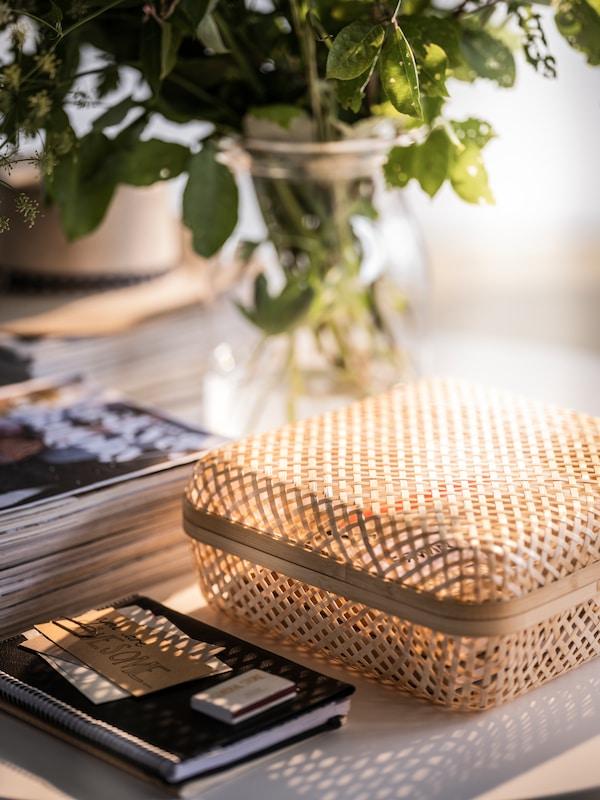 une boîte de rangement en bambou smarra est posée sur une table à côté d'une table