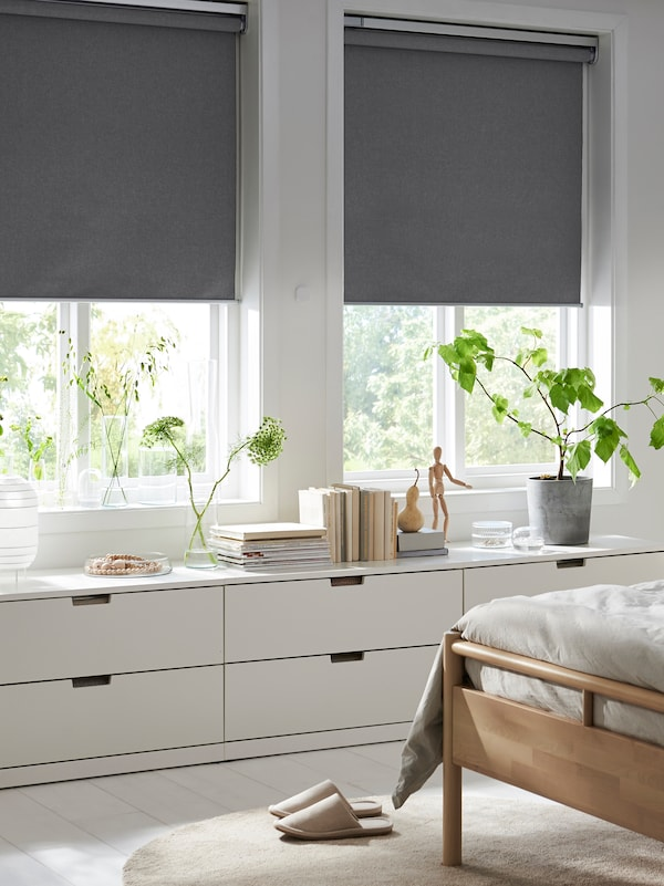 A bedroom with two FYRTUR block-out roller blinds, half-way down, in two windows above three low chests of drawers.