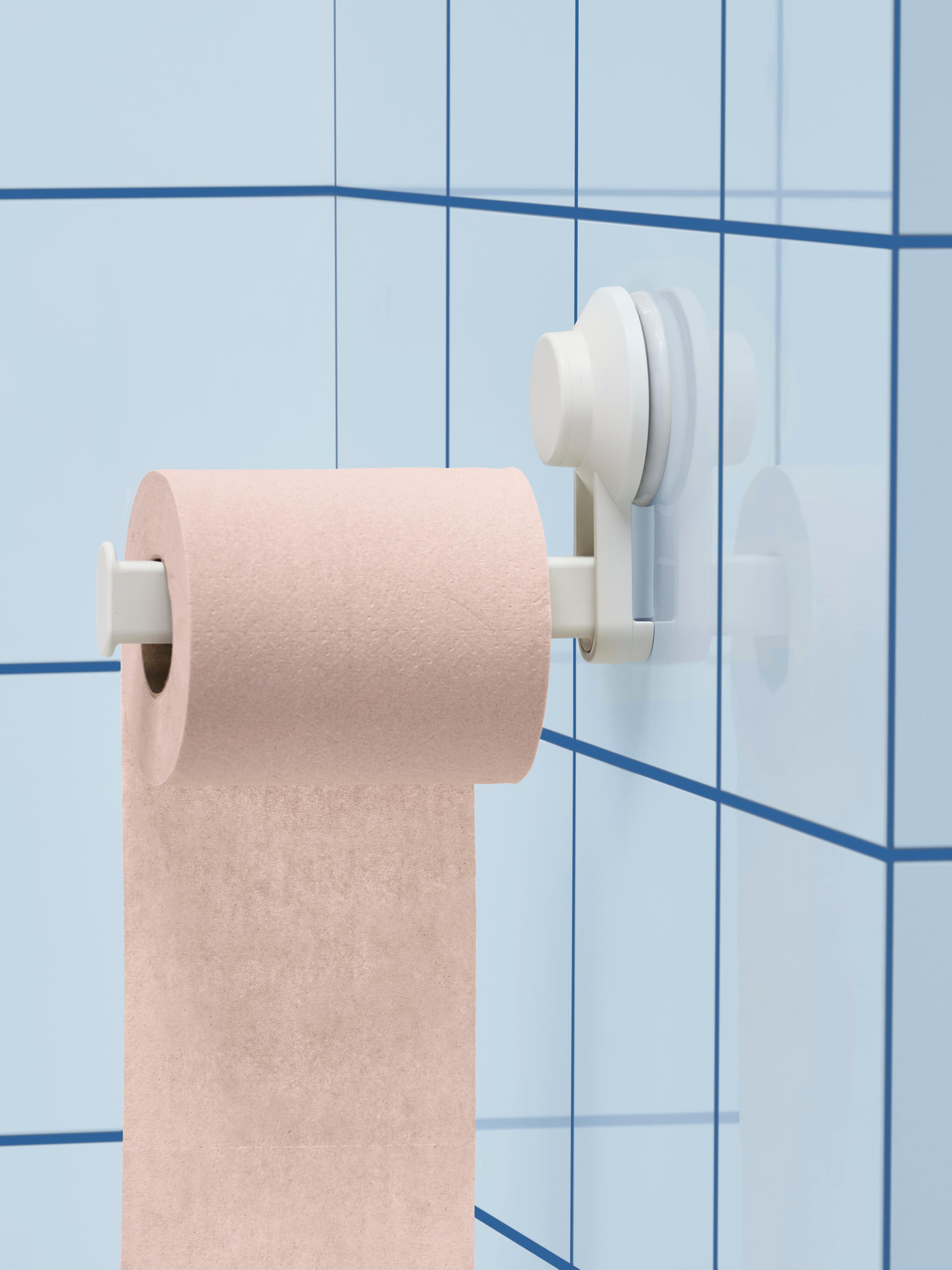 Carta igienica rosa su un portarotolo con ventosa TISKEN in plastica bianca, montato su una parete con piastrelle blu.