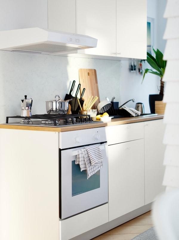 Una cucina KNOXHULT bianca con mobili base e un pensile. Nel forno c'è una torta e sul piano cottura una pentola.