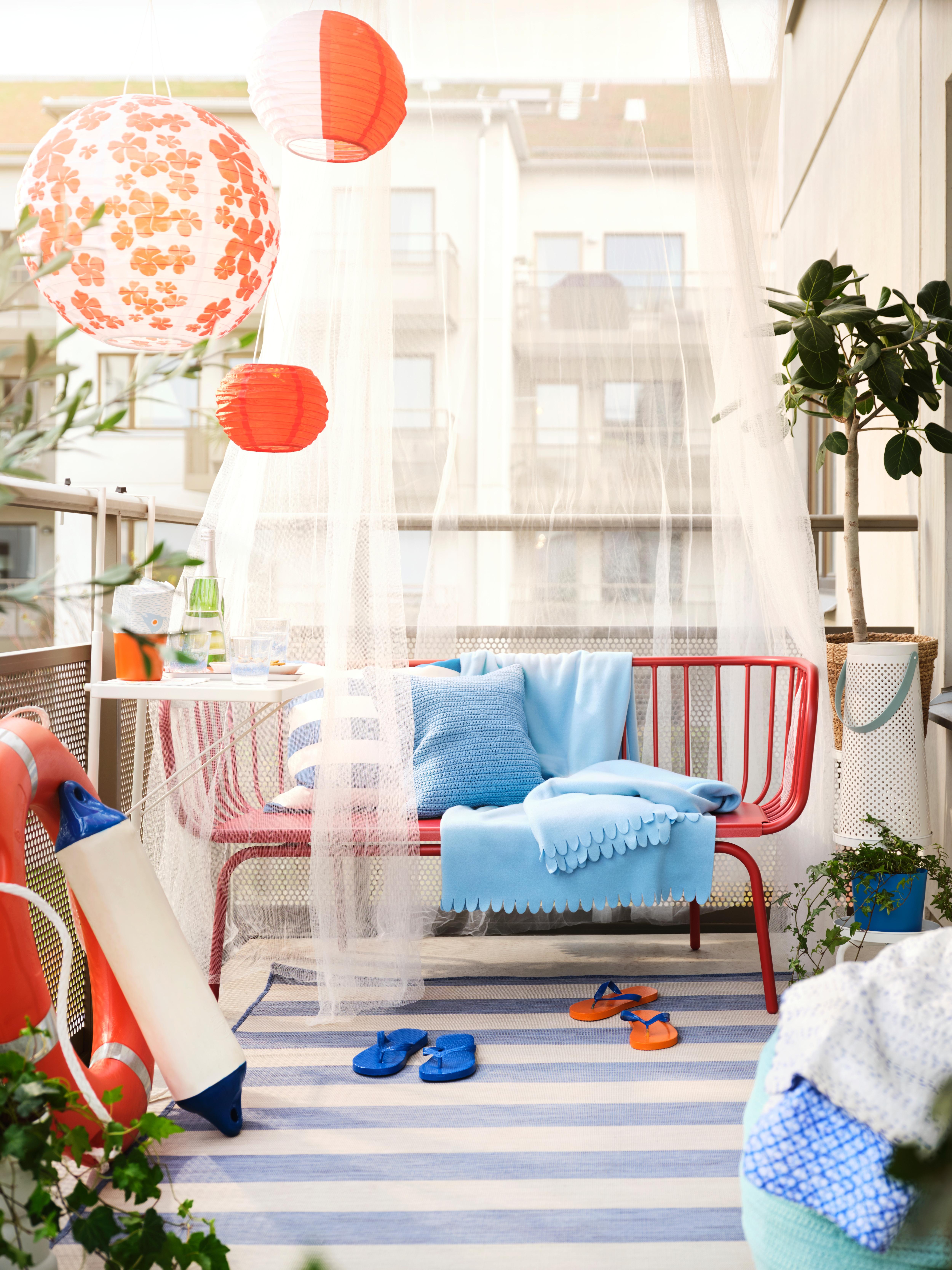 BRUSEN kanpoko sofa gorria, kuxin eta mantak urdin argiekin, SOLVINDEN eguzki LED lanparak eta landareak balkoian.